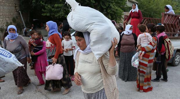 Displaced Iraqis from the Yazidi community arrive at the Mountains of Shikhan near Dahuk, 260 miles north west of Baghdad (AP)