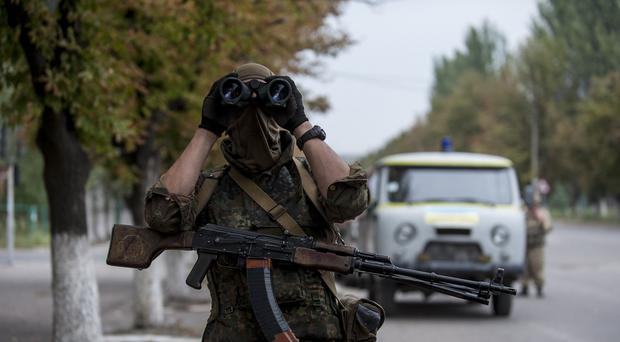 A Ukrainian government soldier looks through a binocular at a checkpoint next to their positions near Donetsk. (AP Photo/Evgeniy Maloletka)