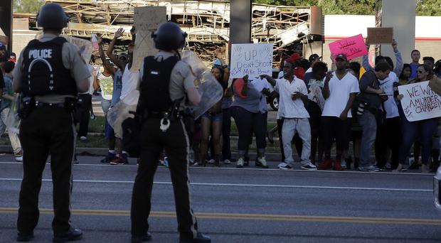 Protesters yell at police in Ferguson, Missouri, after an unarmed teenager was shot (AP)