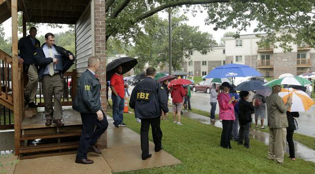 FBI agents leave an apartment building next to a makeshift memorial for Michael Brown where the teenager was shot (AP)