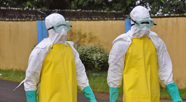 Health workers wearing protective gear go to remove the body of a person who is believed to have died after contracting the Ebola virus in the city of Monrovia (AP)