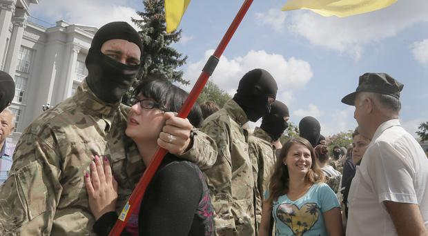 Friends and relatives say goodbye to volunteers in Kiev before they are sent to eastern Ukraine to join a battalion fighting pro-Russian separatists (AP)