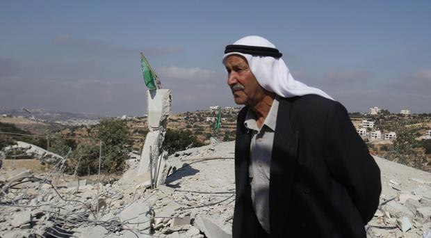 A man stands near the rubble of the house of Hussam Qawasmeh, one of three Palestinians identified by Israel as suspects in the killing of three Israeli teenagers (AP Photo/Nasser Shiyoukhi)