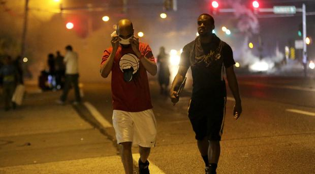 Men walk away from a cloud of tear gas during a protest for Michael Brown in Ferguson (AP)