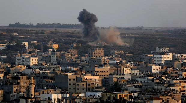 Smoke and dust rise after an Israeli airstrike hit Gaza City (AP)
