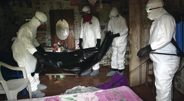 A burial team wearing protective clothing retrieves the body of a 60-year-old Ebola victim in his home in Liberia