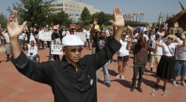 Michael Washington holds his hands in the air during an Oklahoma City in response to the shooting of Michael Brown (AP)