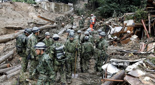 Members of Japan's Self-Defense Force search for survivors in the rubble of a mud-hit residential area following a massive landslide in Hiroshima (AP/Kyodo News)