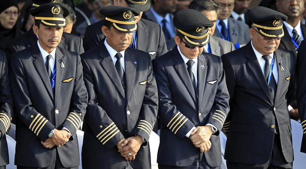 Malaysia Airlines pilots pay tribute to the victims at Kuala Lumpur International Airport (AP)