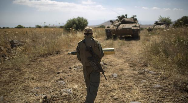 A soldier carries a shell to his tank on the Israeli side of the Golan
