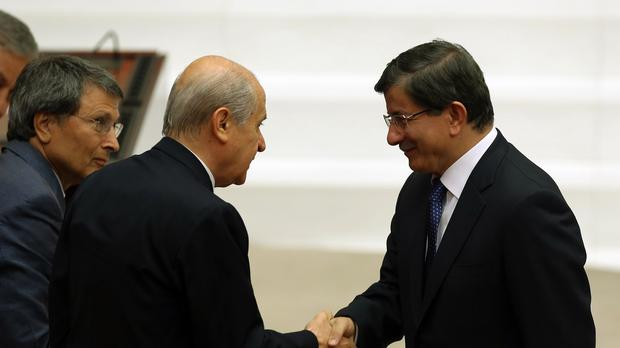 New Turkish prime minister Ahmet Davutoglu, right, shakes hands with opposition Nationalist Action Party leader Devlet Bahceli at the parliament in Ankara (AP Photo/Burhan Ozbilici)