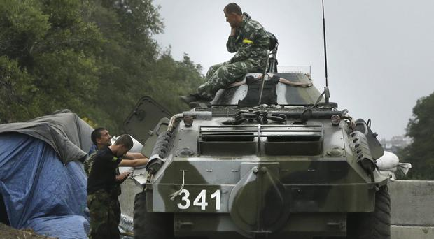 Ukrainian forces guard a checkpoint in the town of Mariupol (AP)