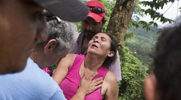 A distraught Margarita Mendez is helped by friends while she waits for news of her son Salvador Urbina, one of the miners trapped at El Comal (AP)