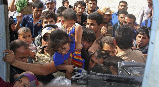Shiite Turkmens try to board an Iraqi Army helicopter aid flight bringing in supplies to Amirli (AP)