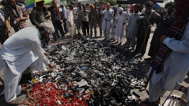 Pakistani protesters gather around a pile of empty tear gas canisters fired by police during a protest near prime minister's home in Islamabad (AP)