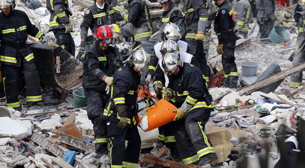 French firemen find a victim in the rubble of a building in Rosny-sous-Bois, outside Paris (AP)