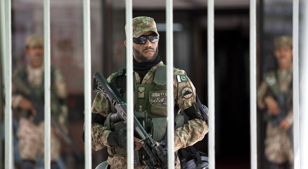 Pakistani army soldiers stand alert inside the parliament building during an emergency session in Islamabad (AP)