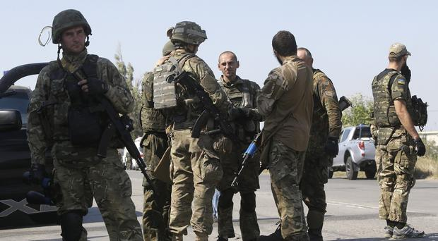 Soldiers of special battalion Azov talk at a checkpoint in the port city of Mariupol, south-eastern Ukraine (AP)