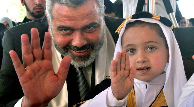 Ismail Haniyeh of Hamas meets a child in Gaza City (AP)