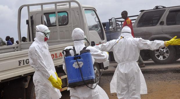 Health workers spray each other with disinfectant chemicals following a suspected Ebola virus death in Monrovia, Liberia (AP)