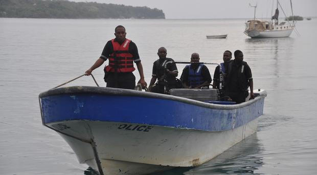 Jamaican marine police return to the Port Antonio Marina after a fruitless search for a plane that crashed into the ocean (AP)