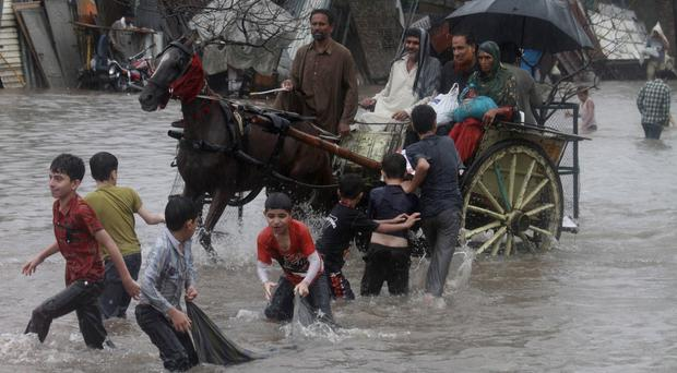 People make their way through a flooded road caused by heavy rain in Lahore, Pakistan (AP)