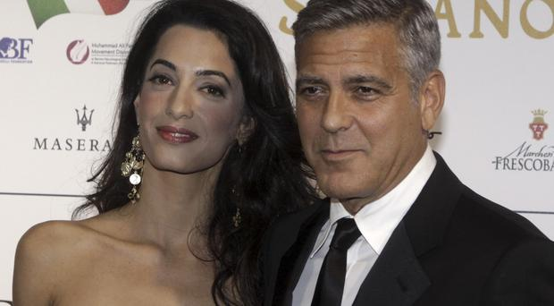 George Clooney and Amal Alamuddin arrive at a foundation gala dinner in Florence (AP)