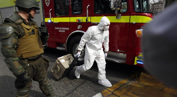 A police forensic expert arrives to the blast site at a subway station in Santiago, Chile (AP)