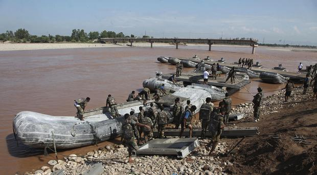 Indian soldiers build a temporary bridge across a river after the existing bridge was damaged in the floods (AP)