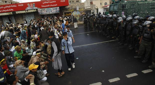 People sit on the ground to prevent riot police vehicles advancing during a protest in Sanaa, Yemen (AP)