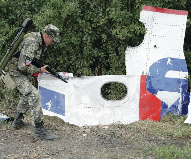 A Pro-Russian rebel looks at debris from flight MH17 near the village of Rozsypne, Ukraine yesterday