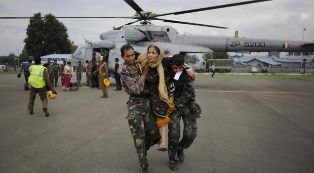 Indian soldiers carry a rescued flood victim at the Air Force Station in Srinagar (AP)