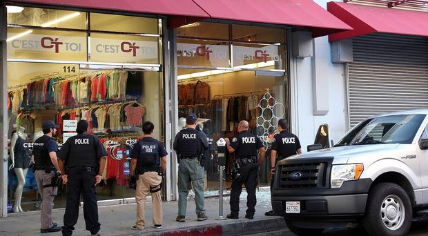 Law enforcement agents stand outside a clothing store after a raid in the Los Angeles fashion district (AP)