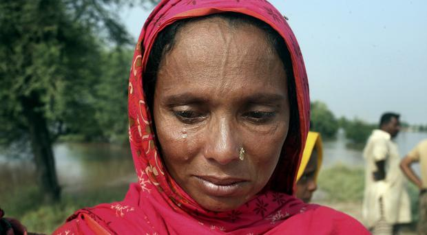 Pakistani villager Arshad Bibi cries while waiting for a boat to evacuate flooding along the Chenab River in Jhang, Pakistan (AP)