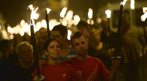 People hold torches during a march for the independence of Catalonia in Barcelona on Wednesday (AP)