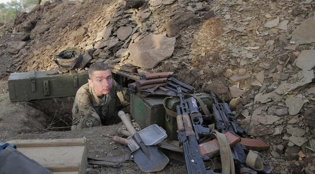A Ukrainian army soldier examines his shelter at a position in Debaltsevo in the Donetsk region. (AP)