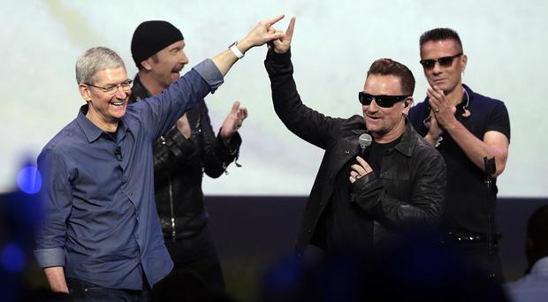 Apple chief executive Tim Cook, left, greets Bono after U2 performed at an Apple event (AP)