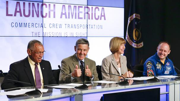 Members of a panel are all smiles as they announce Nasa's choice of Boeing and SpaceX to ferry astronauts to the International Space Station (AP)