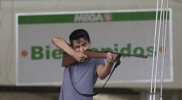 An employee from Mega Supermarket fires an air rifle at people trying to loot the store in Los Cabos (AP)