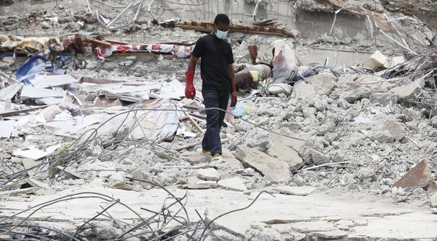Rescue workers search for survivors in the rubble of a collapsed building in Lagos, Nigeria (AP)