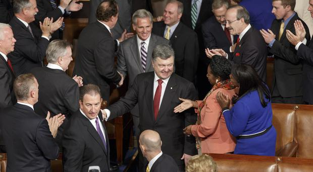 Ukrainian president Petro Poroshenko is welcomed by US politicians as he arrives to address a joint session of Congress at the Capitol in Washington (AP)