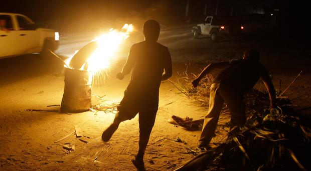 Youths light a bonfire inside a steel drum, while they protect their homes in Los Cabos (AP)
