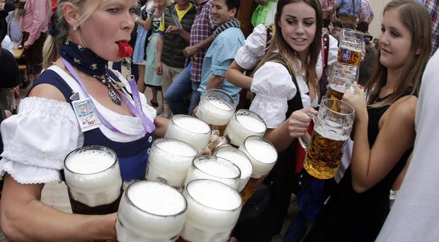 A waitress carries beer mugs during the opening of the 181st Oktoberfest beer festival in Munich