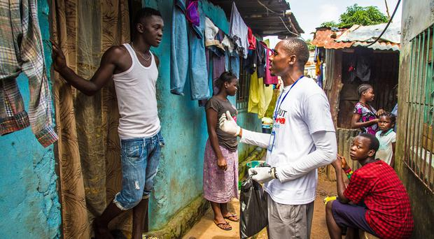 A health worker volunteer talks with a resident on how to prevent and identify the Ebola virus in others in Freetown, Sierra Leone (AP/Michael Duff)