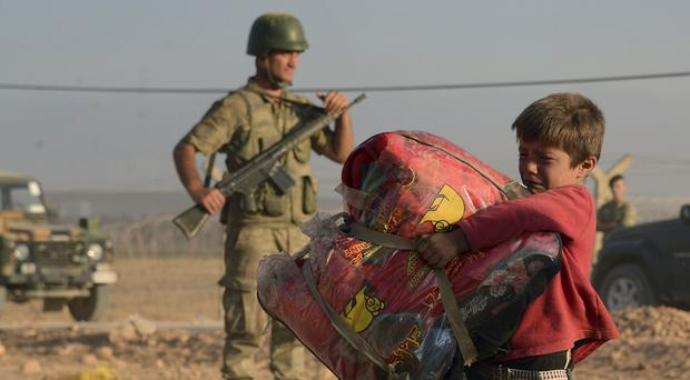 Turkish soldiers stand guard as a Syrian refugee boy carries his belongings at the border (AP)