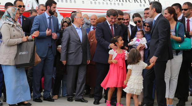 Turkish Prime Minister Ahmet Davutoglu with freed hostages at the airport in Ankara (AP)