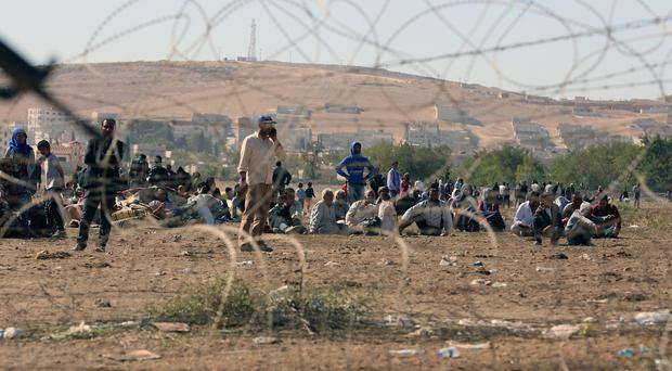 Syrian refugees wait at the border in Suruc, Turkey (AP)