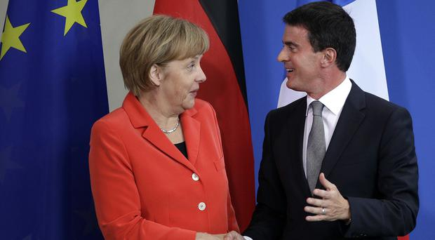 German Chancellor Angela Merkel greets French Prime Minister Manuel Valls in Berlin (AP)