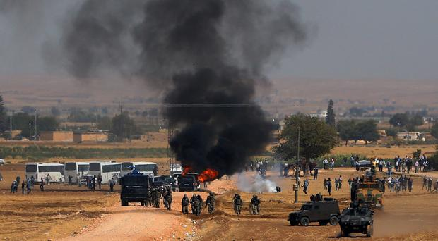 A car burns as riot police use tear gas to disperse Kurdish demonstrators as thousands of Syrian refugees arrive at the border in Suruc, Turkey (AP)