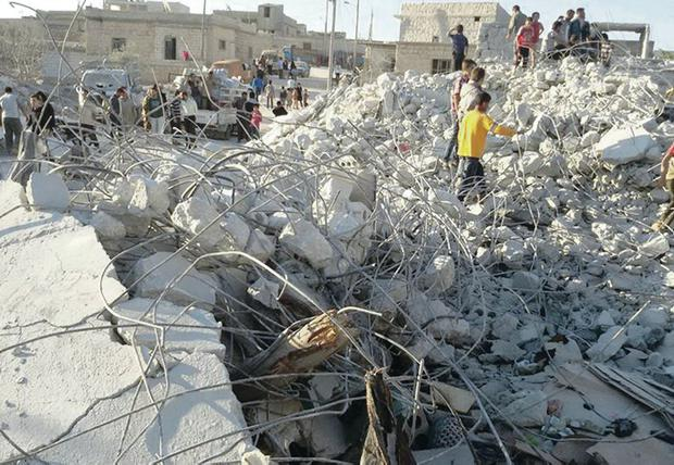Syrian citizens inspect a damaged house that was targeted by coalition air strikes in the village of Kfar Derian